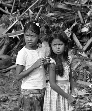 Two young girls next to rubble and debris