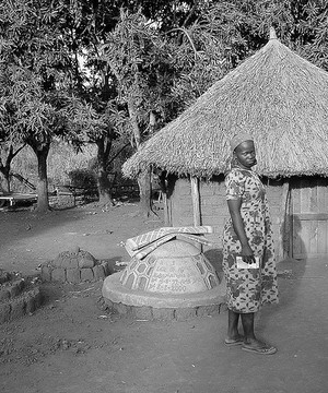 African woman standing next to her village home.