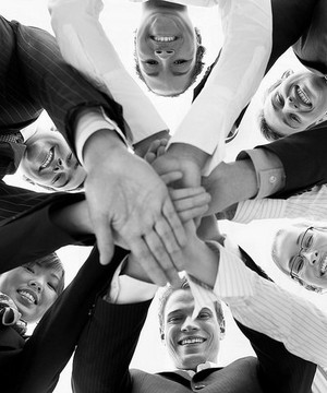 Group of people putting their hands together in a circle