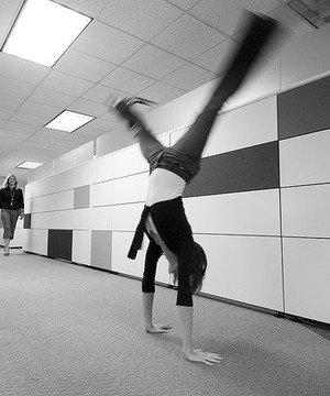 Woman doing a cartwheel in an office