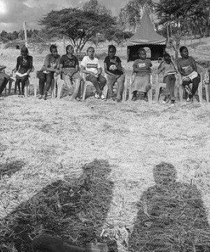 A group of African men and women sat in a semi circle.