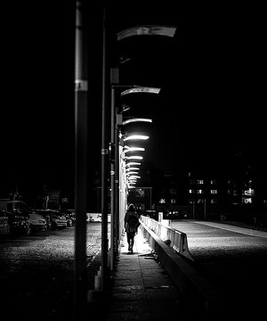 Woman walking alone along a street at night.