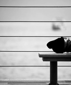 Man asleep on a bench.