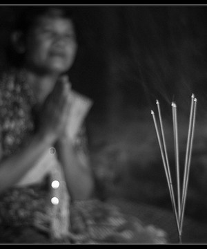 Cambodian woman praying with incense sticks