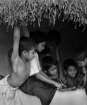 Children in remote village huddled around a laptop.