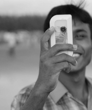 Young man holding his phone to the camera and looking directly into it and smiling.