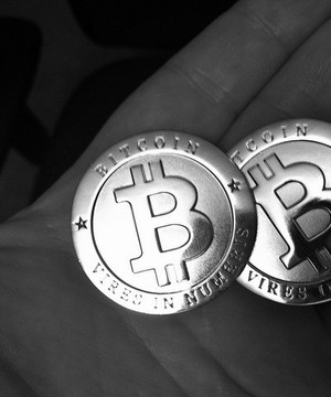 Two gold bitcoins held in someones palm