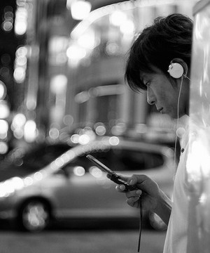 Man with headphones on stops and looks at his phone on side of busy Tokyo street