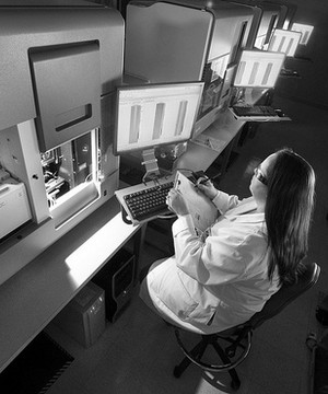 A female scientist sat in a laboratory analysing various computer screens