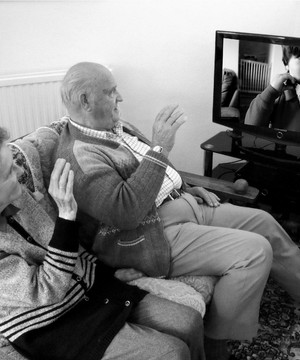 An elderly couple speaking to their grandchild through a SpeakSet set-top box