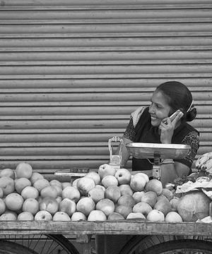 Indian lady selling fruit from a cart, talking on a mobile phone