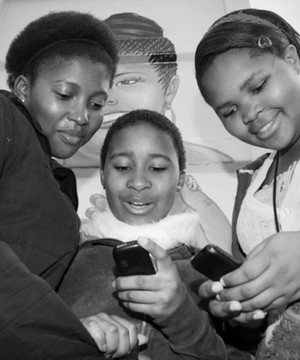 Three local students looking at mobile phones.