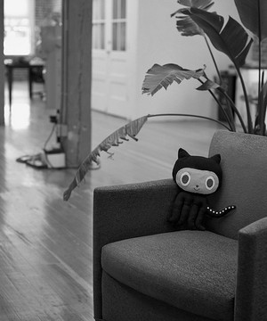 A fabric Github mascot toy sat on a chair in the Github office.
