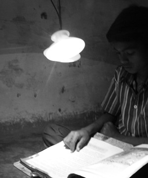 A boy reading in the dark using only a GravityLight