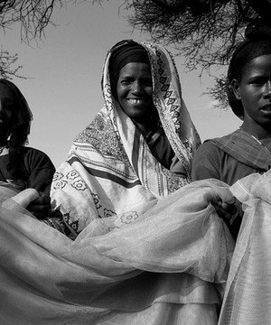 Women in Ethiopia laying out mosquito nets