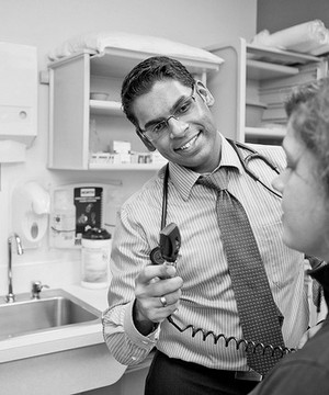 Male doctor with stethoscope talks to patient