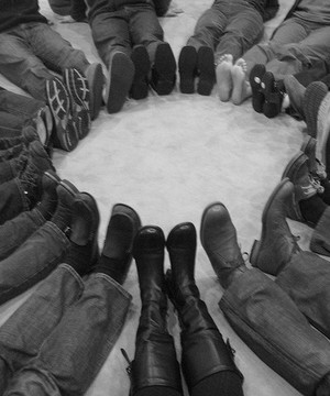 People sat in a circle on the floor with their pointing inwards, depicting a peaceful protest