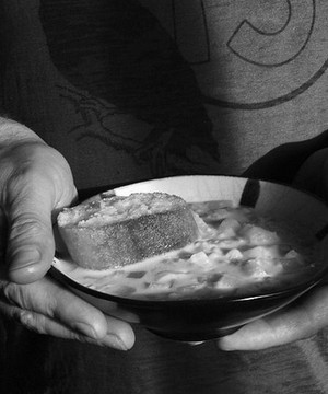Man holding a bowl of corn chowder
