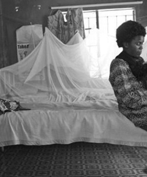 An African mother and child sat on a hospital bed