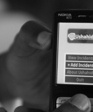 Close up of someone holding up a mobile phone with the Ushahidi platform open on the screen