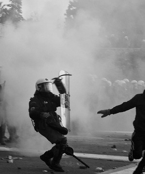 A man in a balaclava runs away from riot police in an Athens street