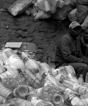 Two local merchants watch over a plastic bottle depot in Malawi.