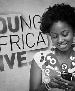 A young African person smiling and looking at her phone