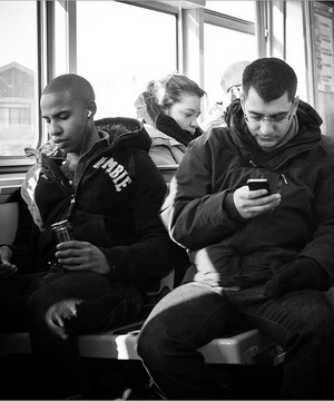 People sat on a bus, one man looking at his mobile phone