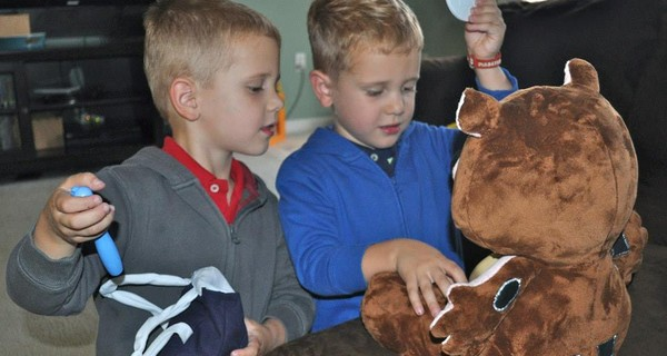 Two young boys interacting with Jerry the Bear
