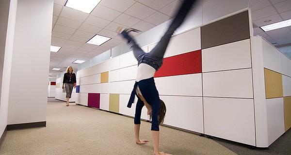 Woman doing a cartwheel in an office
