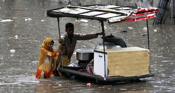 Man and woman pushing trolley in floods