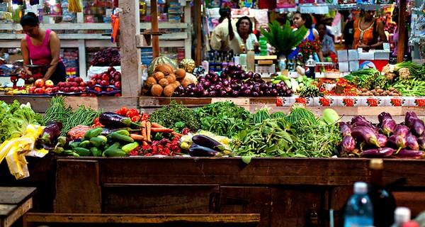 Two women walk past a street market selling fruit in Uruguay, South America