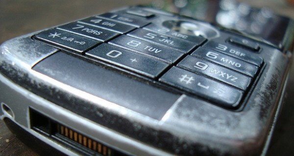 A close up of an old, well-used mobile phone