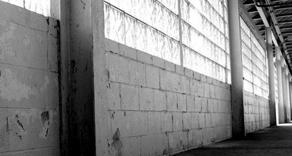 Black and white image of a concrete and glass block wall in a derelict building