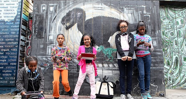Members of Black Girls CODE stood in front of graffiti wall with their laptops
