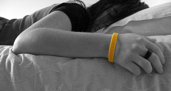 Woman laying on bed wearing a Livestrong wristband