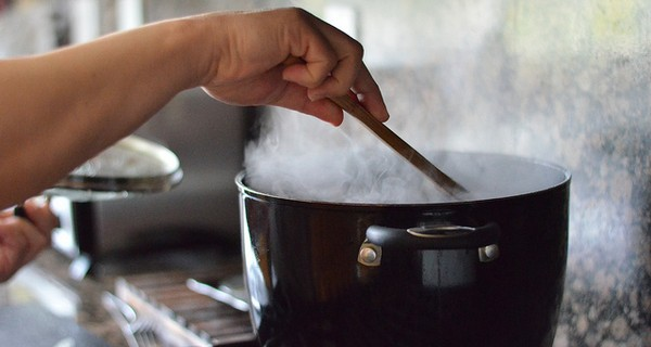 A close up of someone stirring a simmering saucepan