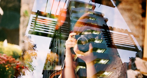 A reflection of a woman taking a photograph of a window with striking architecture in the background