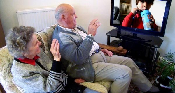 An elderly couple speaking to their grandchild through a SpeakSet set-top box