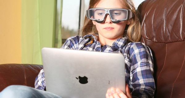 A girl wearing eye tracking glasses whilst working on a laptop