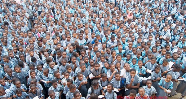 A large crowd of Nigerian school children look up towards the camera