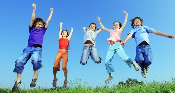 Five children in colourful clothing jumping in the air