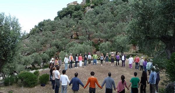 A group of people stood in a circle holding hands