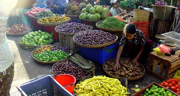 Burmese market stall with lady selling vegetables