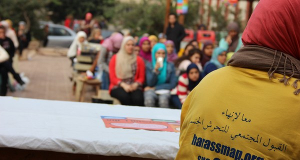 A close up of a HarassMap protester sporting a sign that reads: 'private property, no touching'