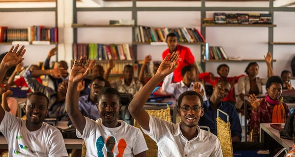 Students with raised hands in the classroom