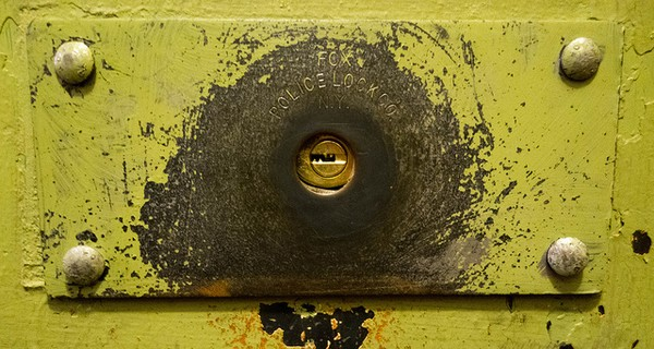 Metal lock painted yellow and inscribed with 'Fox Police Lock Co. N.Y'