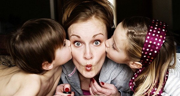 A mum facing the camera while two children kiss her on the cheeks
