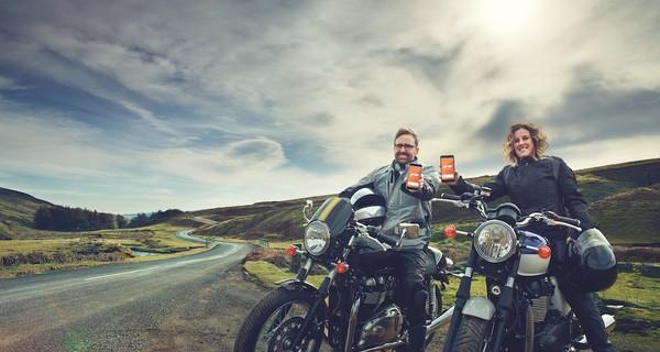 Two people sat on motorbikes alongside an open road.