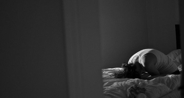 Woman sat on her bedroom with her head in her hands